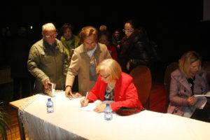 Firmando ejemplares al término del acto